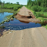 Crumbling road covered with water