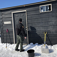 officer knocking on fish house door