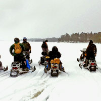 group of snowmobilers out on a lake