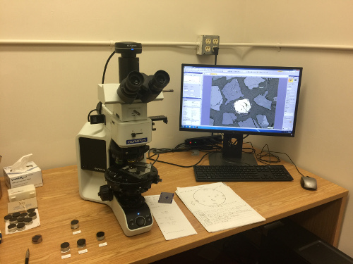 Desk set up with reflected light microscopy unit including a microscope, computer, and mineral samples