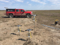 Red truck parked next to a series of three geological probes