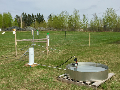 A weather station made up of various probes and measurement devices set up on a grass lawn
