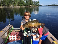 photo of boy with a smallmouth bass caught in a Northern Minnesota lake with rocky shorelines.