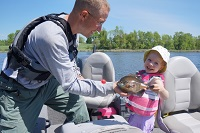 man holding large flathead catfish caught shore fishing along river