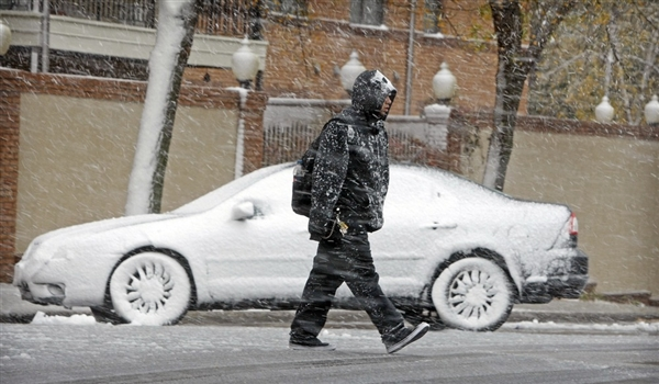 Snow coats cars and pedestrians in Fargo on October 4, 2012