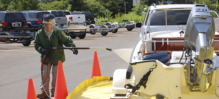 DNR employee spraying a boat at a courtesy decontamination site