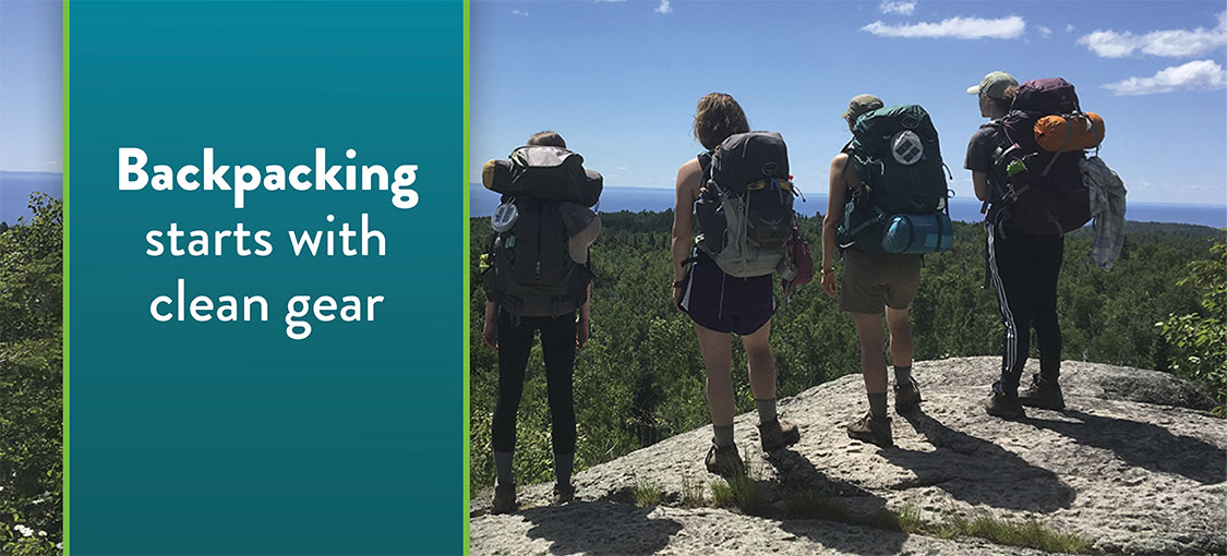 four people with backpacking standing on overlook