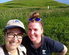 megan benage and jess petersen sitting in a prairie field, smiling at the camera