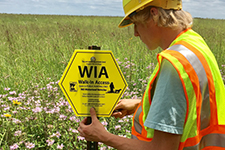dnr employee wearing bright work vest and hard hat installing a wia sign in a prairie