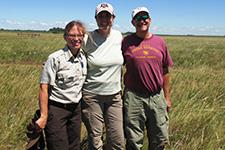 USFWS Biologist, Sara Vacek, TNC Prairie Ecologist, Marissa Ahlering, and DNR Ecologist, Daren Carlson hug at the Chippewa Prairie Preserve after completing a grassland monitoring team survey.