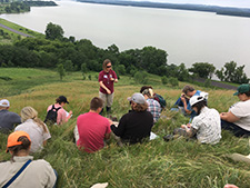 USFWS Biologist, Sara Vacek, offers support to a group of land managers by helping them identify plants at a prairie training