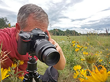 Prairie Ecologist, Chris Helzer, kneels in a prairie to photograph some incredible subjects!