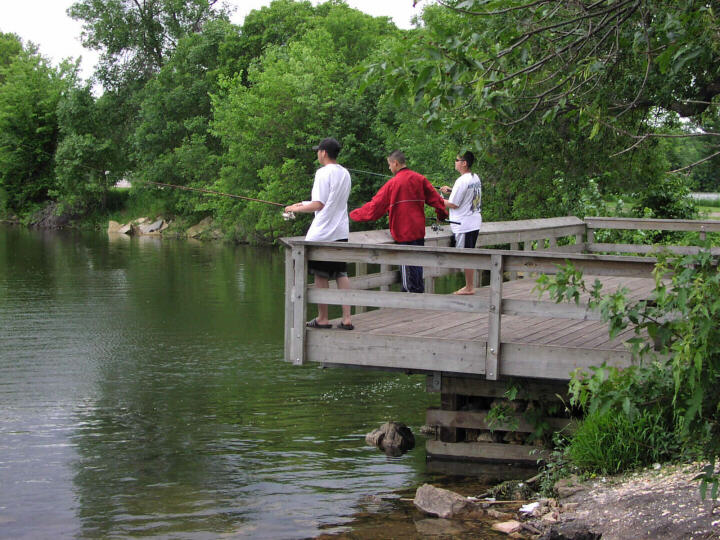 Three people fishing from the fishing platform on the north end of Lake Phalen.