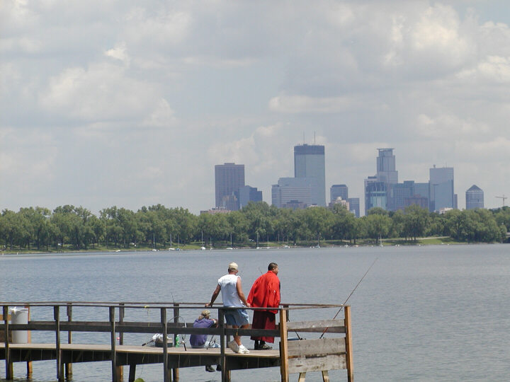 Three people fishing from the Lake Calhoun fishing pier with the Minneapolis skyline visible across the lake.