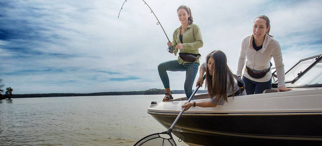 Three women fishing off the front of a boat and trying to net a fish.