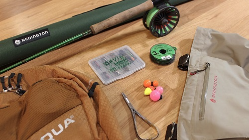 Photograph of a fly rod and reel, fly line, backing line and five different trout flies.