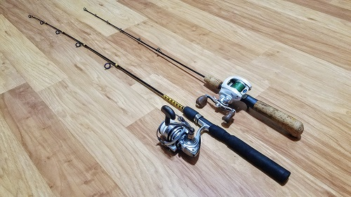 Photograph of two ice fishing rod and reels combinations. One rod has spinning reel on it and the other a bait-casting reel.