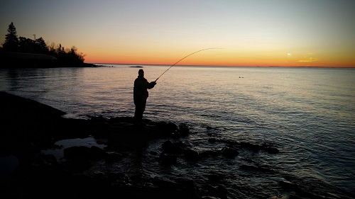 Photograph of angler standing on Shore of Lake Superior at sunrise holding a rod and reel.