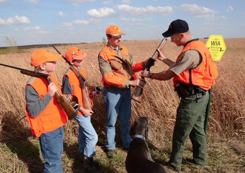 An hunter ed instructor shows a student how to properly carry a shotgun in the field