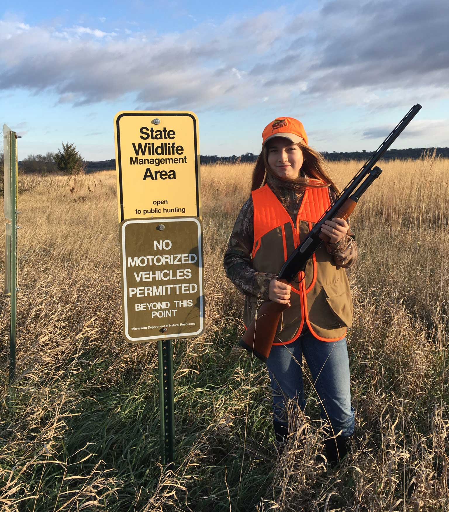 Pheasant hunter at a Wildlife Management Area sign