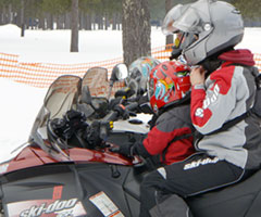 photo of an adult and child in full safety gear on a snowmobile