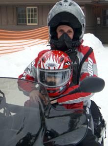 Photo of a parent and child in full safety gear, atop a snowmobile