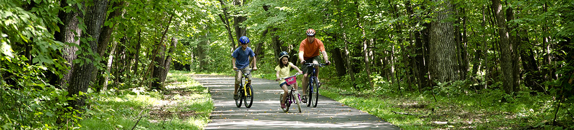 two visitors biking down a trail