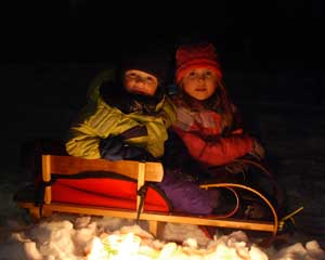 bundled up kids in a sled at night