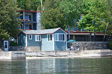 cabin along a waterfront, with a covered boathouse on the beach