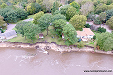arial view of two cabins along a waterfront, shoreline is eroding