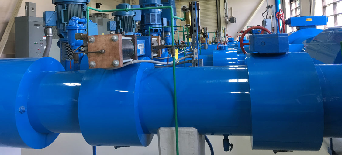 interior of a large water supplier with a network of huge bright blue water pipes.