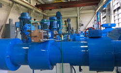 large blue pipes in the foreground on a background of blue pipes and gages in a municiple water facility