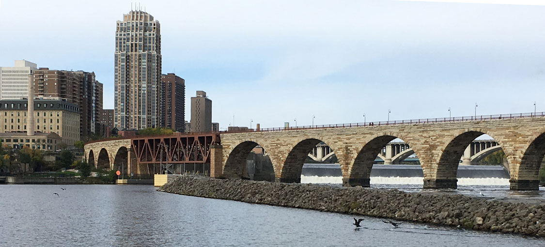 Stone arch bridge over the Mississippi with the Minneapolis skyline behind it