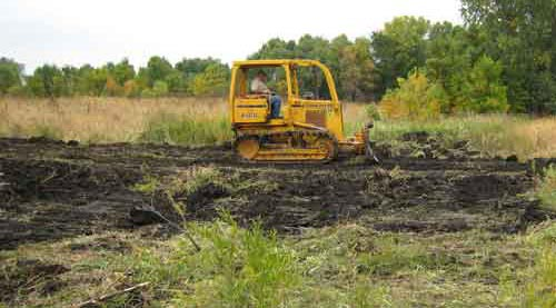 A bulldozer prepares ground for habitat enhacement.