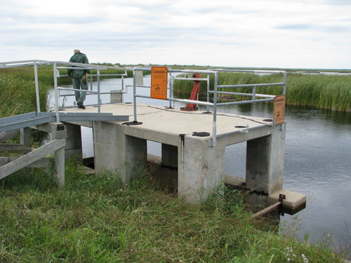 Checking a water control structure in the Roseau River area.