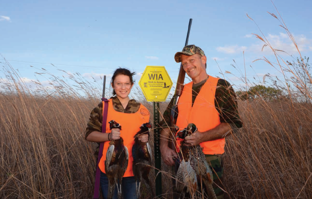 Two successful pheasant hunters hold up the birds they harvested.