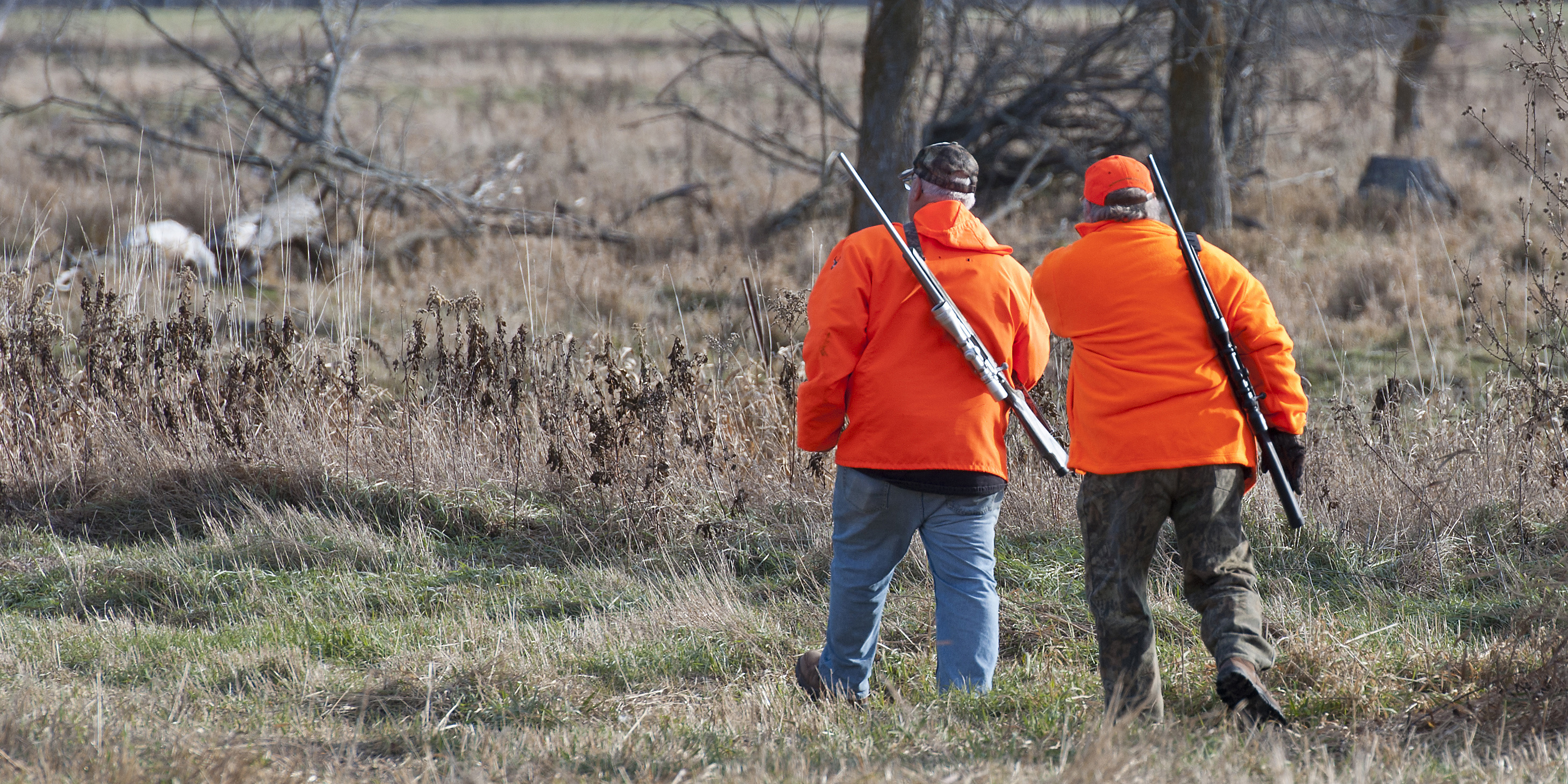 Hunters dressed in blaze orange walking in November.