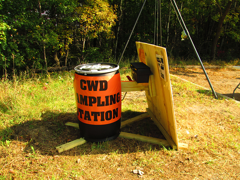 Black barrel wrapped in an orange sign with CWD SAMPLING STATION in black lettering.