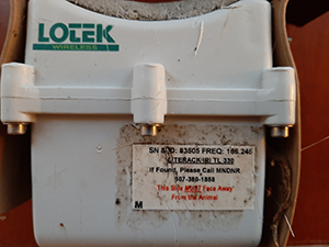 Collar showing label with contact information and serial number on lower right of the unit.